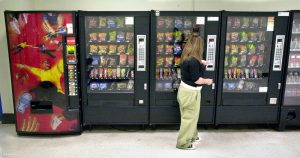 Lady using a vending machine as provided for by Automatic vending machine services in Swansea